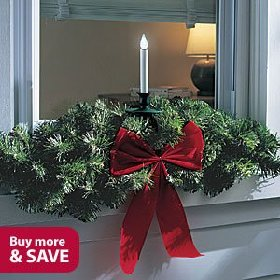 this outdoor light sensitive led candle comes with a lush artificial christmas window sill swag and under window bracket for easy decorating